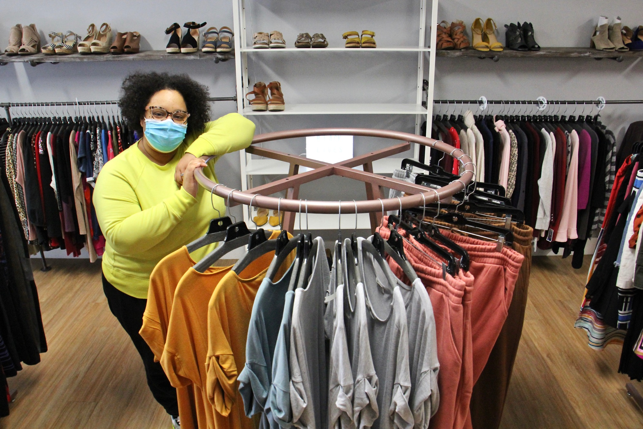 Adrienne Ray smiles while wearing a mask next to a circular rack of clothing