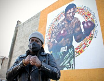 Artist Ernel Martinez is the creator of 'Heart of a Champion' a tribute to Philadelphia boxer Joe Frazier. The mural at 13th Street and Allegheny Avenue was sponsored by Mural Arts Philadelphia. (Emma Lee/WHYY)