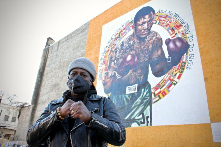 Artist Ernel Martinez in front of a mural of Philadelphia boxer Joe Frazier