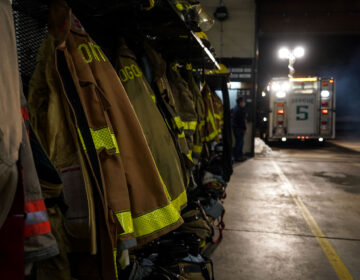 Firefighter coats are lined up, with an ambulance in the background