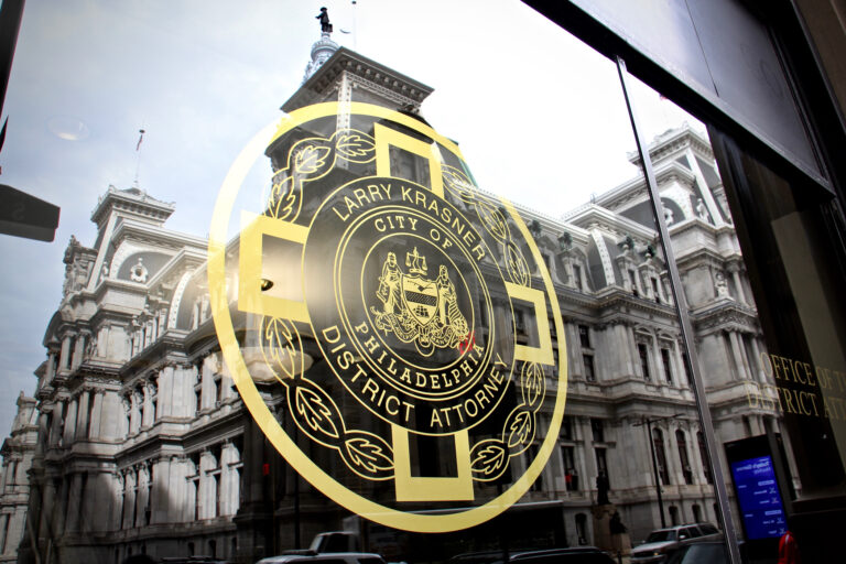 Philadelphia City Hall is reflected in the windows of the Office of the District Attorney