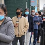 A line forms outside the Center for Architecture and Design on Arch Street where Nationalities Service Center was holding a COVID-19 vaccination clinic. (Emma Lee/WHYY)
