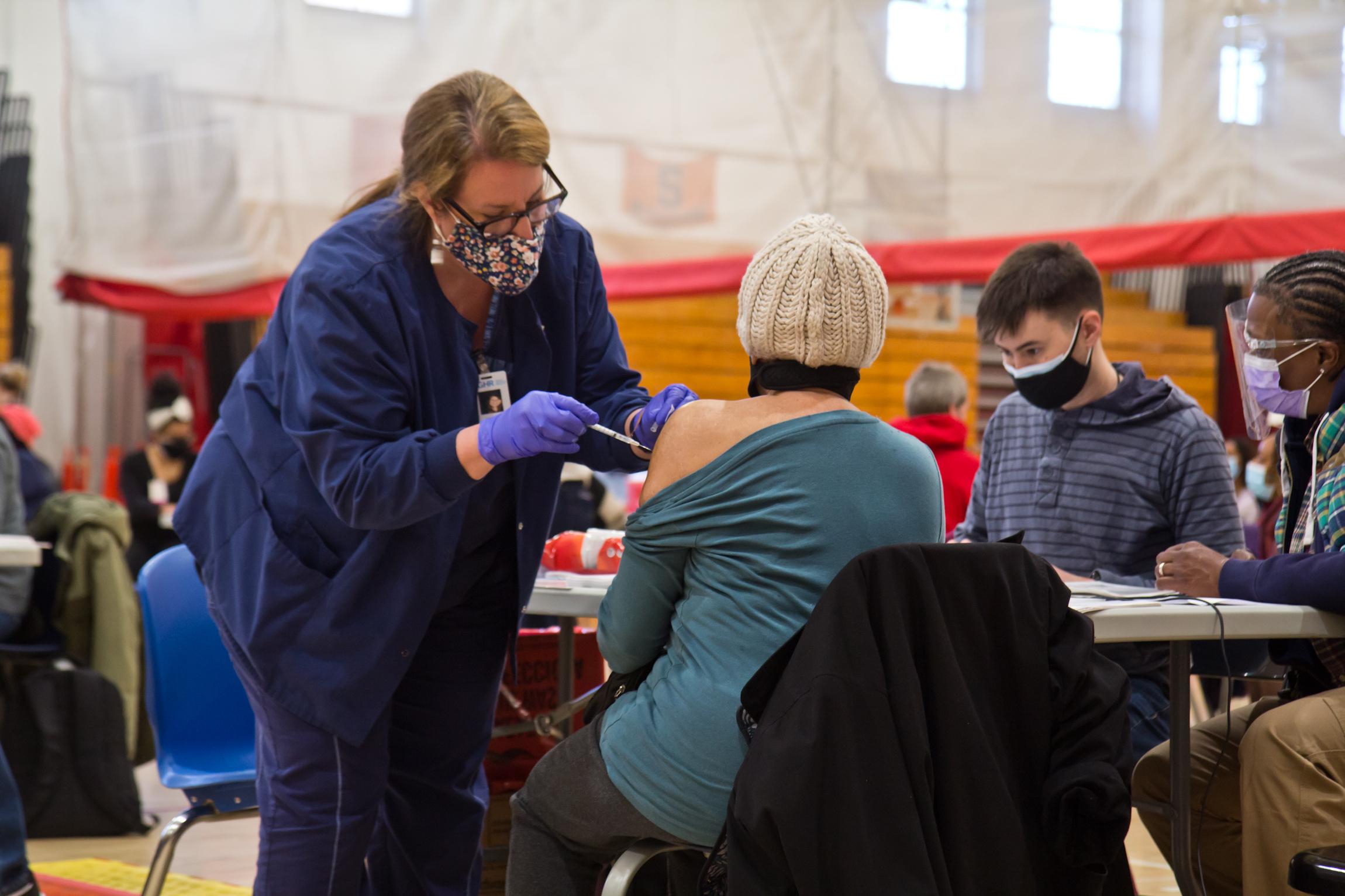 A resident of Philadelphia's Nicetown neighborhood receives the COVID-19 vaccine