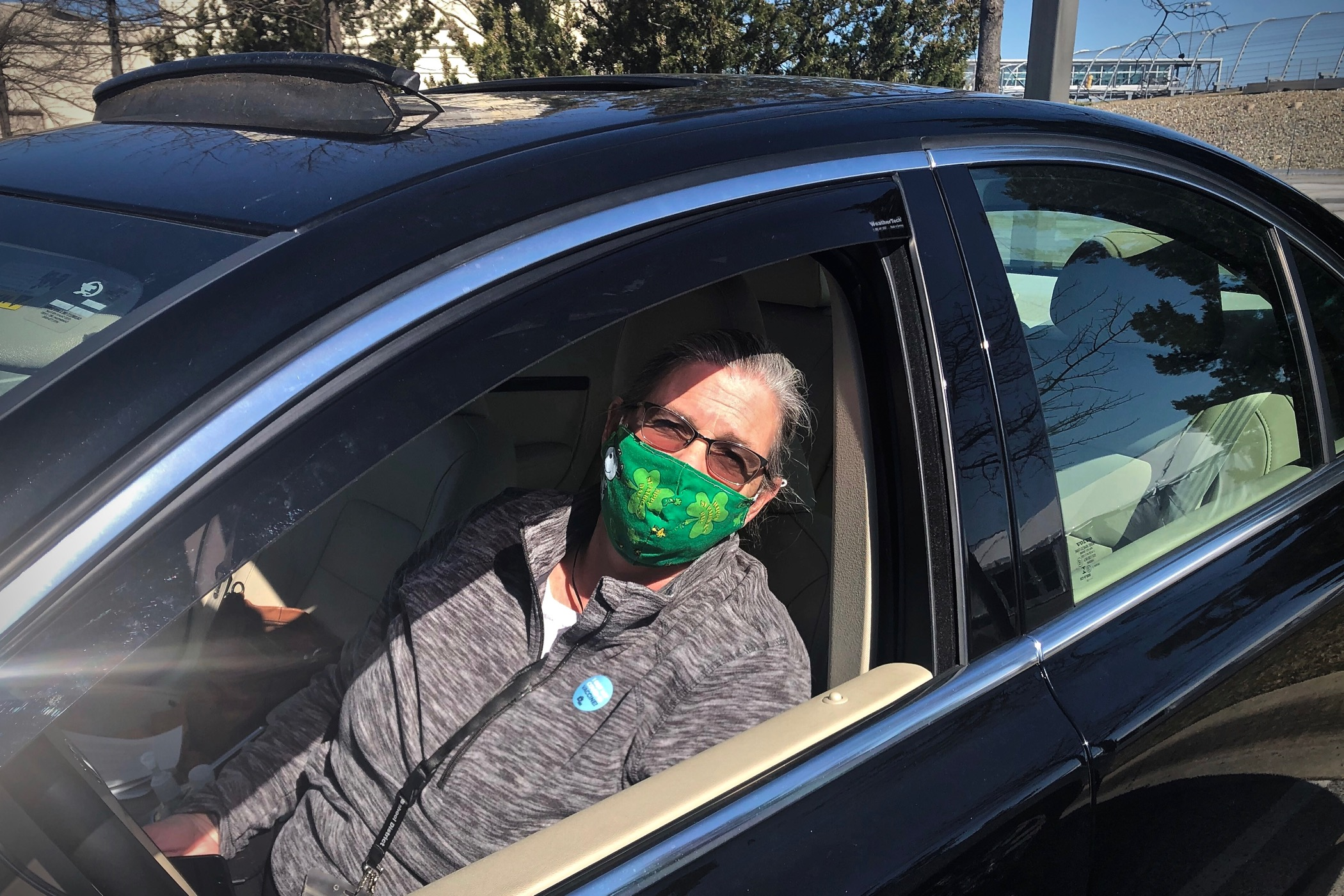 Susan Smith wears a face mask while sitting inside her car