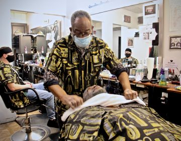 Leroy Robinson Jr. tends to a customer at Leroy's Barbershop on Lancaster Avenue. (Emma Lee/WHYY)