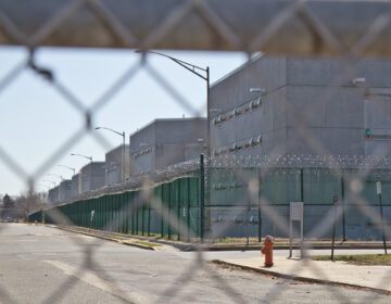 The exterior of Curran-Fromhold Correctional Facility as seen through a fence