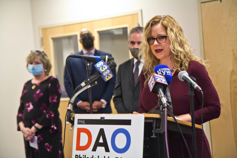 Kimberly Esack addresses the press from a DAO podium