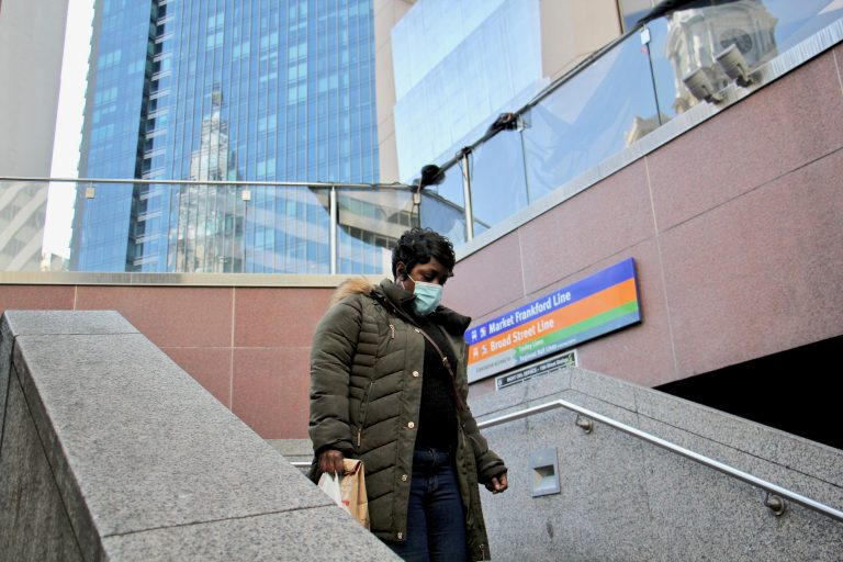 A rider descends the stairs to the 15th Street subway station, across the street from City Hall. (Emma Lee/WHYY)