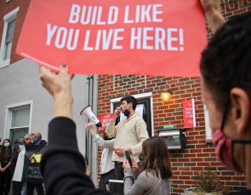 Adrian Bondy, a leader of the Build Like You Live Here neighborhood organization, speaks to protesters during a rally at 2400 East Huntingdon Street. A seven-story building is planned for that address in a neighborhood of two- and three-story rowhouses. (Emma Lee/WHYY)