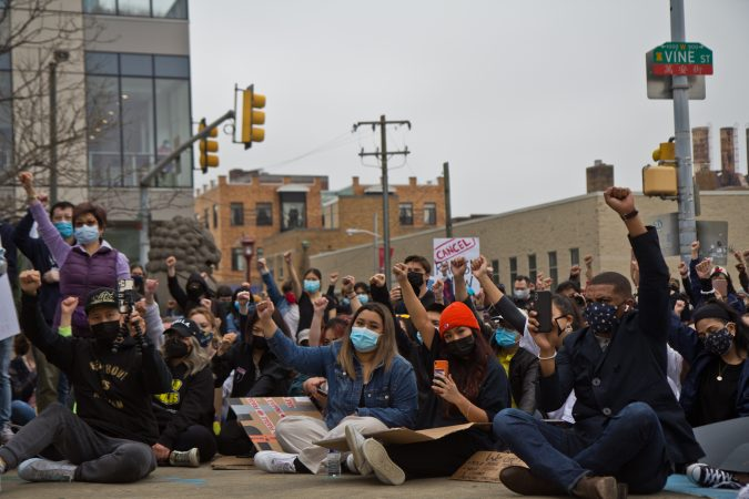 Participants at a solidarity rally at 10th and Vine streets raised fists against white supremacy and violence against their communities on March 25, 2021. (Kimberly Paynter/WHYY)