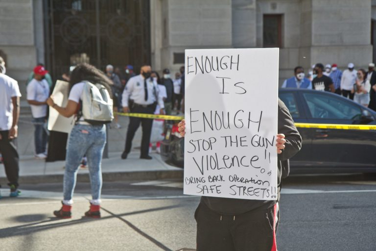 Activists hung caution tape around City Hall in Philadelphia on March 26, 2021, to bring the crime scenes they witness in their neighborhoods to city officials' work place. (Kimberly Paynter/WHYY)