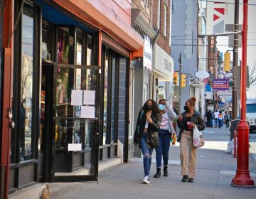 Shoppers walk on South Street. The South Street Headhouse district has so far survived the pandemic, with new businesses replacing those that have closed. (Emma Lee/WHYY)