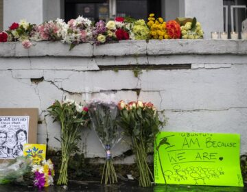 Flowers and signs are displayed at a makeshift memorial outside of the Gold Spa in Atlanta, Wednesday, March 17, 2021. Police in the Atlanta suburb of Gwinnett County say they've begun extra patrols in and around Asian businesses there following the shooting at three massage parlors in the area that killed eight, most of them women of Asian descent. (Alyssa Pointer/Atlanta Journal-Constitution via AP)