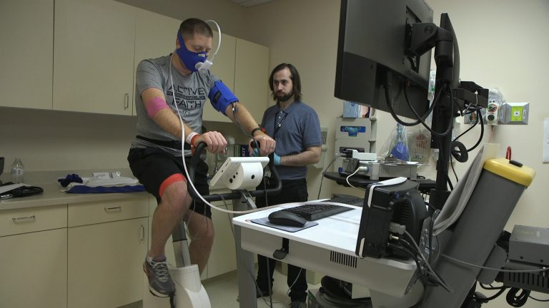 In this Nov. 18, 2019 image from video, Zach Ault of Paducah, Ky., is connected to medical monitors during an exercise test at the National Institutes of Health's hospital in Bethesda, Md. Ault has ME/CFS, what once was called