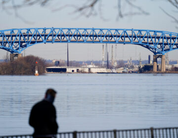 A person walks past the Interstate-95′s mile-long double-decked Girard Point Bridge in Philadelphia, Wednesday, Feb. 24, 2021. (AP Photo/Matt Rourke)
