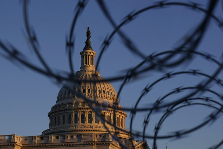 The Capitol is seen through razor wire at sunrise in Washington