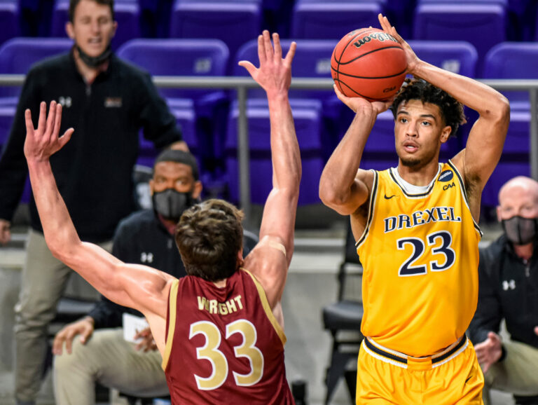 Drexel forward T.J. Bickerstaff (23) shoots over Elon forward Simon Wright (33) during the first half of an NCAA college basketball game for the Colonial Athletic Association men's tournament championship in Harrisonburg, Va., Tuesday, March 9, 2021. (AP Photo/Daniel Lin)