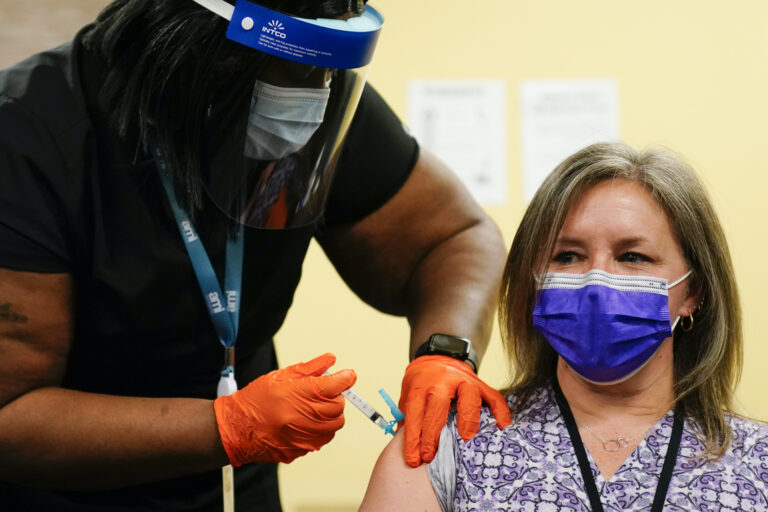 Nurse Monique Bourgeois, left, administers the Johnson & Johnson COVID-19 vaccine to educator Diane Kay at a vaccination site set up setup for teachers and school staff at the Berks County Intermediate Unit in Reading, Pa., Monday, March 15, 2021. (AP Photo/Matt Rourke)