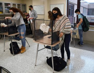 In this March 18, 2021, file photo, students in teacher Christopher Duggan's science class clean their work areas at the end of class at Windsor Locks High School in Windsor Locks, Conn. (AP Photo/Jessica Hill)
