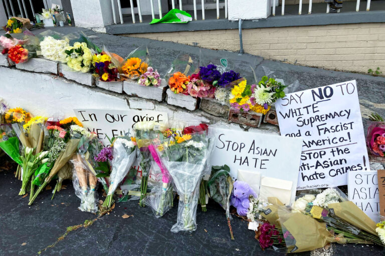 In this March 19, 2021, file photo, flowers, candles and signs are displayed at a makeshift memorial in Atlanta. (AP Photo/Candice Choi)