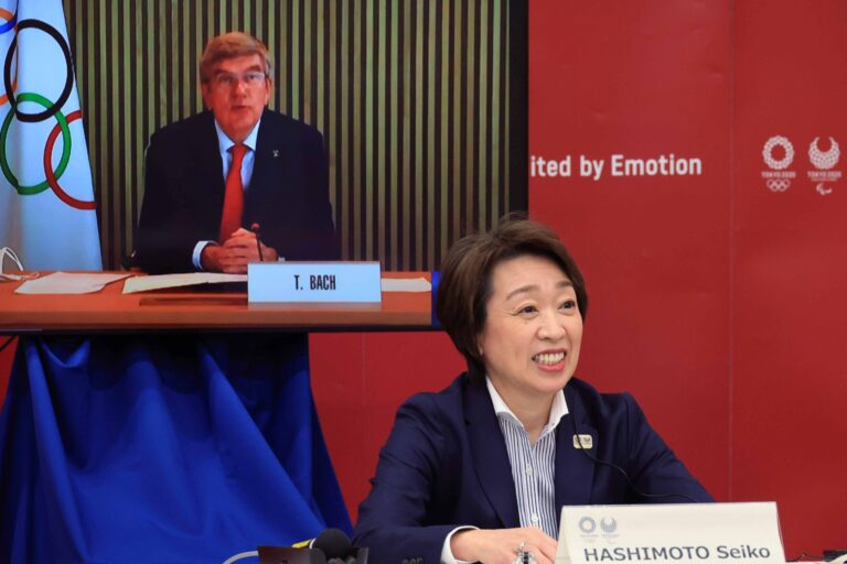 International Olympic Committee (IOC) President Thomas Bach, on a screen, delivers an opening speech while Tokyo 2020 Organizing Committee President Seiko Hashimoto listens  at a five-party meeting of Tokyo 2020 Olympic and Paralympic Games with International Paralympic Committee (IPC) President Andrew Parsons, Tokyo Gov. Yuriko Koike and Japanese Olympic Minister Tamayo Marukawa in Tokyo Saturday, March 20, 2021.  (Yoshikazu Tsuno/Pool Photo via AP)