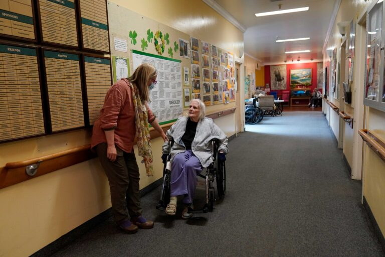 Chaparral House activities director Erika Shaver-Nelson, left, talks with resident Joyce in the hallway at Chaparral House in Berkeley, Calif., Thursday, March 18, 2021. (AP Photo/Jeff Chiu)