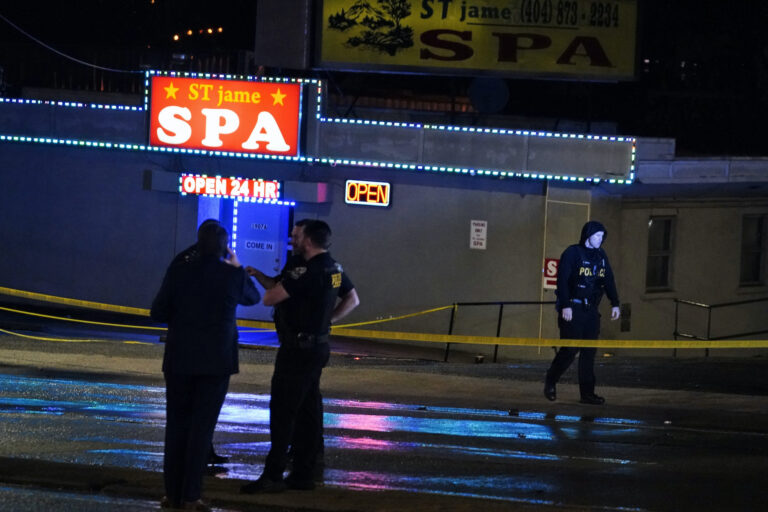 Officials stand in front of a massage parlor after a shooting