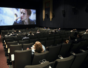 Moviegoers sitting in a socially distant seating arrangement at the AMC Lincoln Square 13 theater