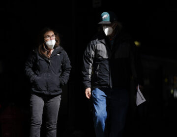 People wearing face masks as a precaution against the coronavirus walk in Philadelphia