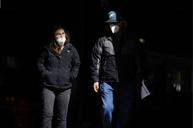People wearing face masks as a precaution against the coronavirus walk in Philadelphia