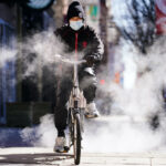 A person wearing a face mask as a precaution against the coronavirus rides a bicycle in Philadelphia