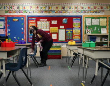 Tia Baker cleans a desk in a classroom