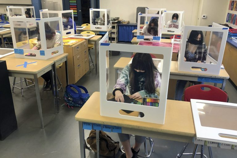 Physically distanced, and with protective partitions, students work on an art project during class