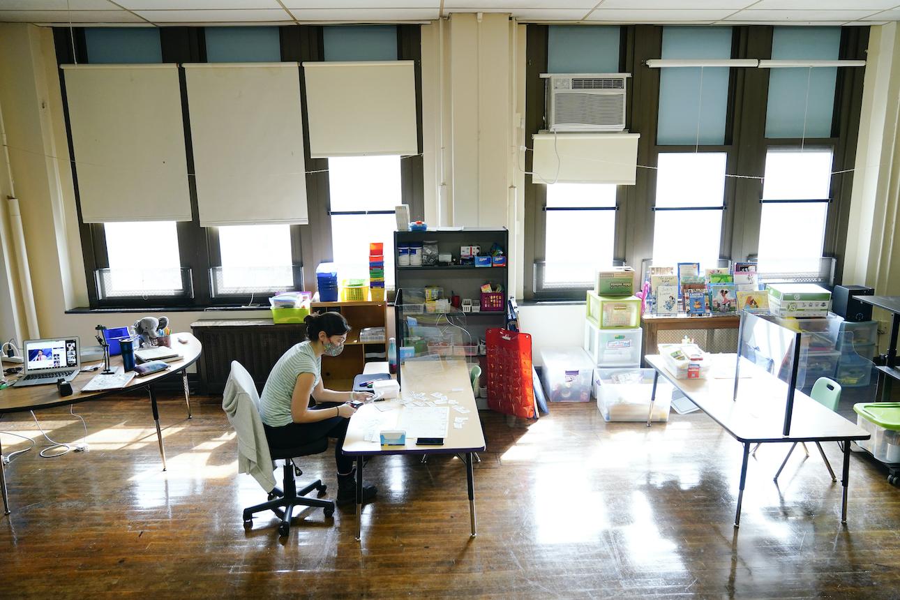 Teacher Laura Bonanni sits at a desk in her kindergarten classroom