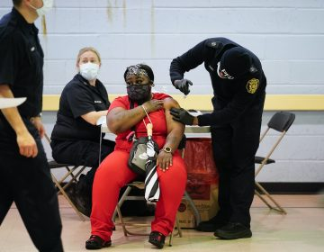 A member of the Philadelphia Fire Department administers the Johnson & Johnson COVID-19 vaccine to a woman at a vaccination site setup