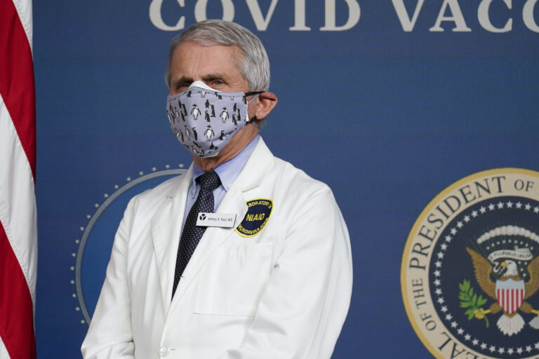Dr. Anthony Fauci wears a face mask and white coat at a COVID-19 briefing