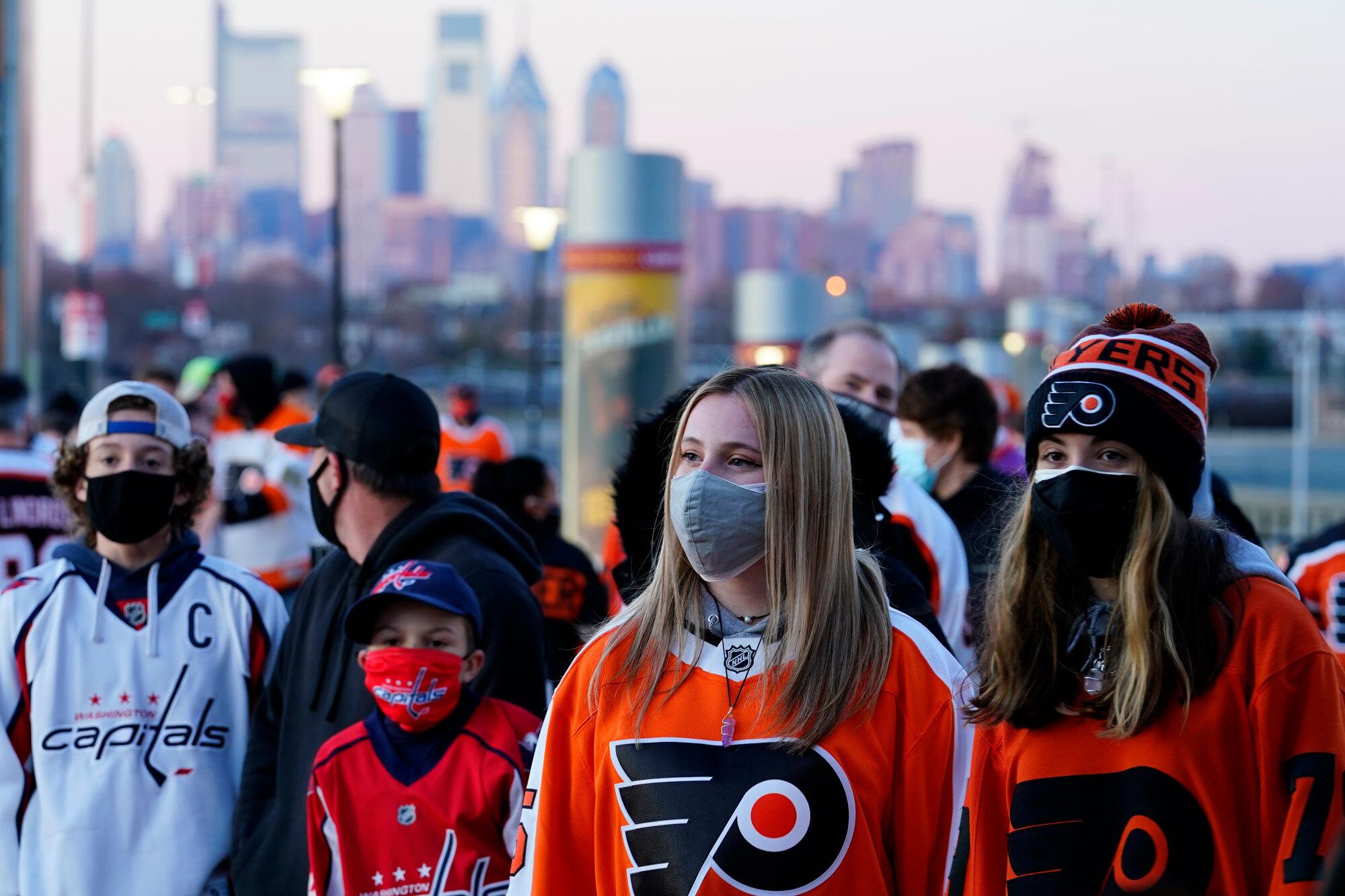 Fans wearing face masks line up outside the Wells Fargo Center