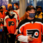 Fans wearing masks walk through security at the Wells Fargo Center