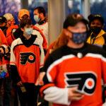 Fans wearing masks walk through security at the Wells Fargo Center
