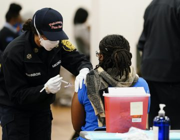 A member of the Philadelphia Fire Department administers a COVID-19 vaccine at a vaccination site