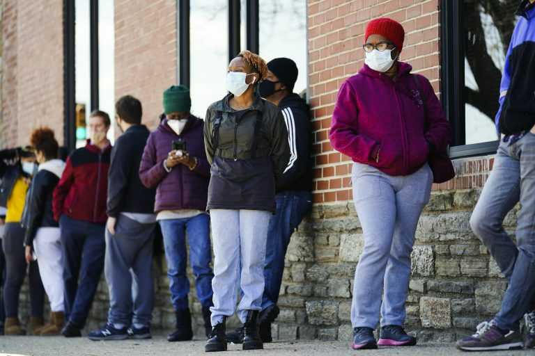 People wearing face masks wait in line to receive COVID-19 vaccines