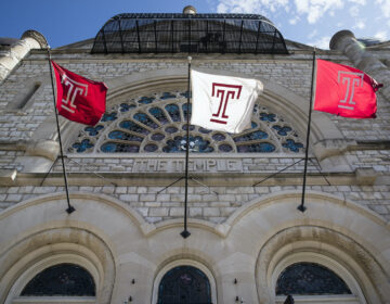 Flags wave in the wind from a building on Temple University's campus