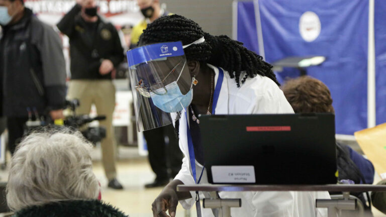 A health worker assists a resident at Passaic County's vaccination site