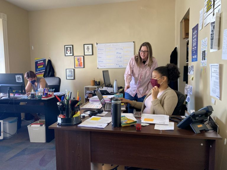 ALDEA executive director Bridget Cambria reviews work of communications and intake assistant Nathalia Cruz in ALDEA's downtown Reading office. (Anthony Orozco/WITF)
