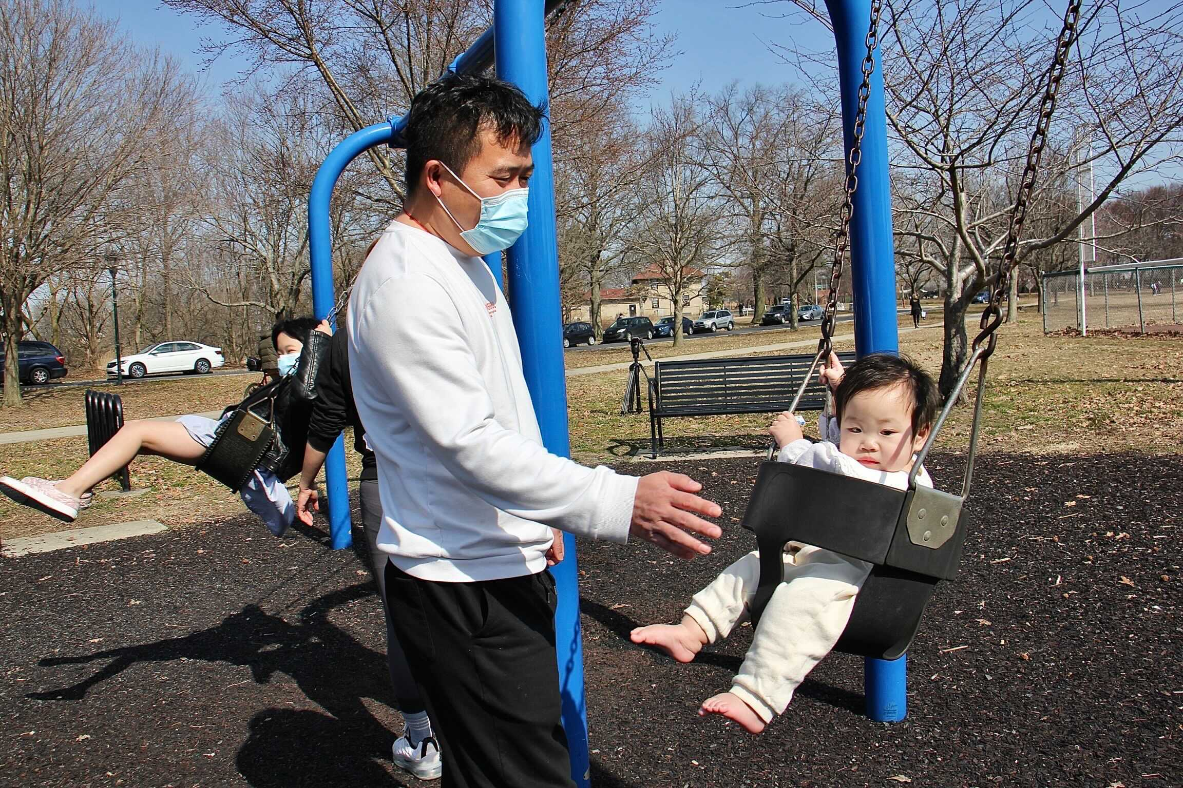 Wu Tan plays with his daughters on a swing set at FDR Park