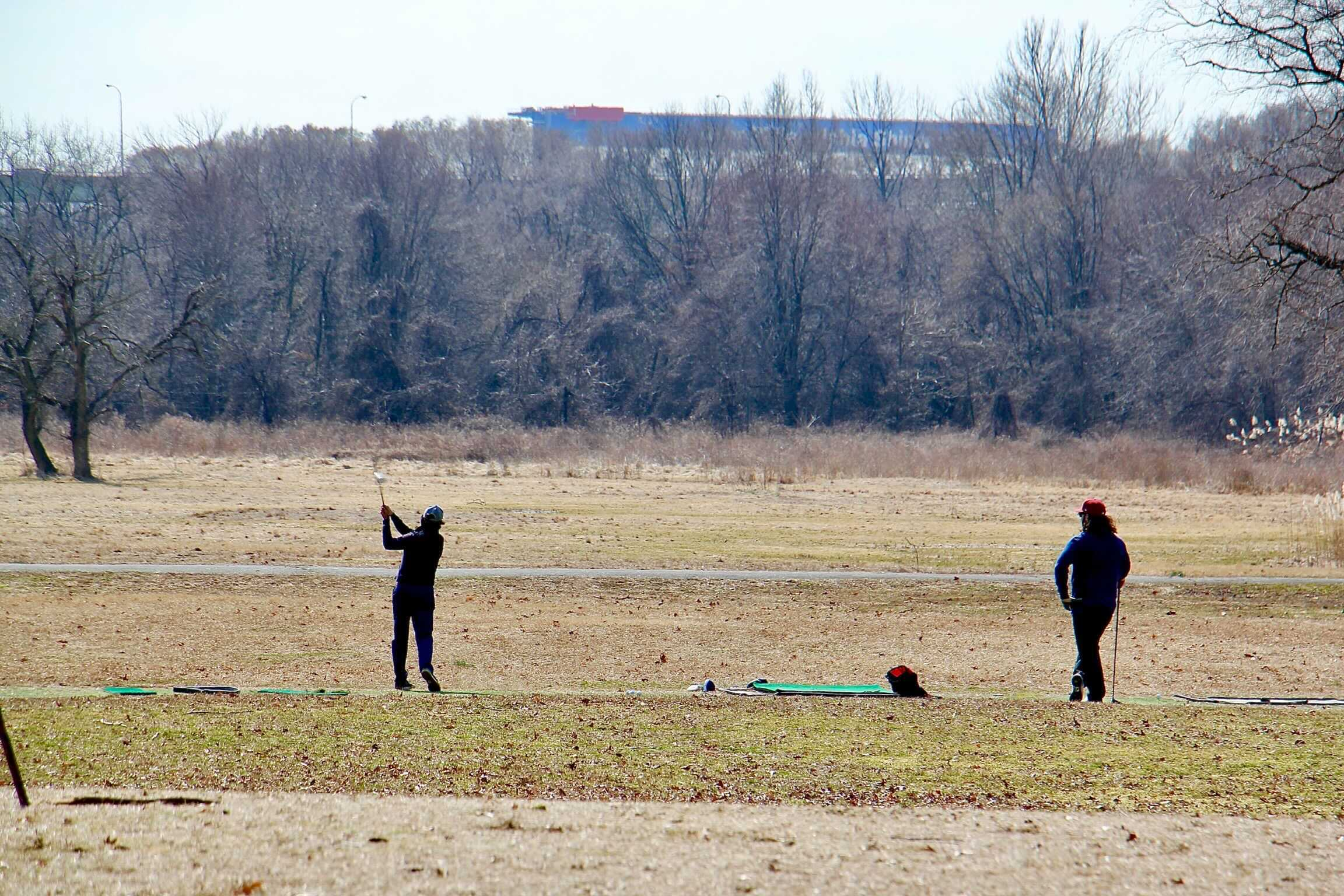 Golfers work on their swings at the abandoned FDR Park golf course