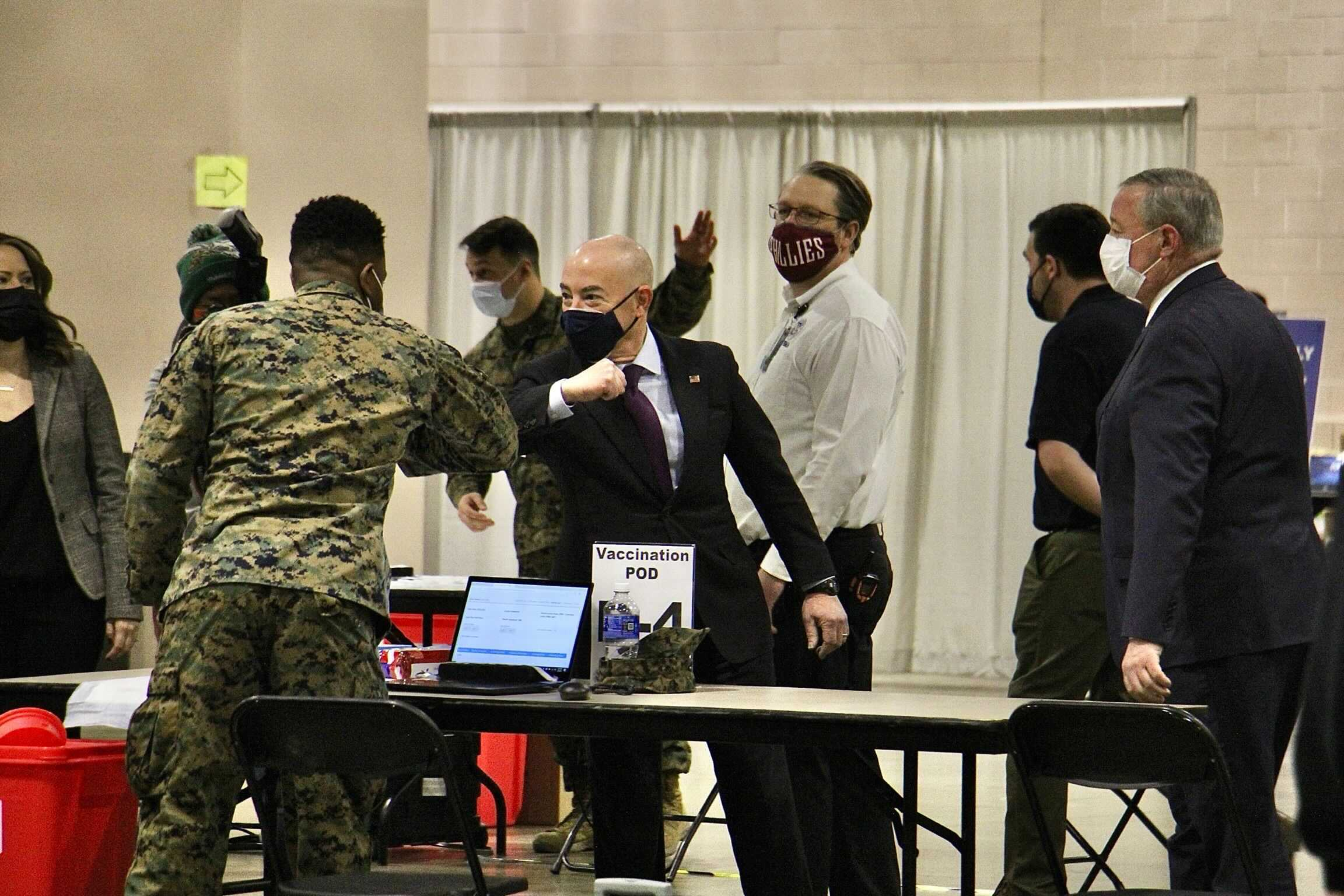 Department of Homeland Security Secretary Alejandro Mayorkas elbow bumps a National Guard member during a tour of FEMA's community vaccination site at the Pennsylvania Convention Center