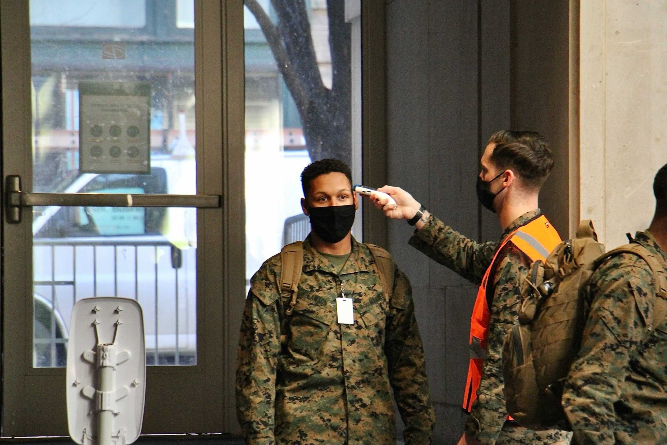 National Guard members undergo a temperature check as they enter the Pennsylvania Convention Center