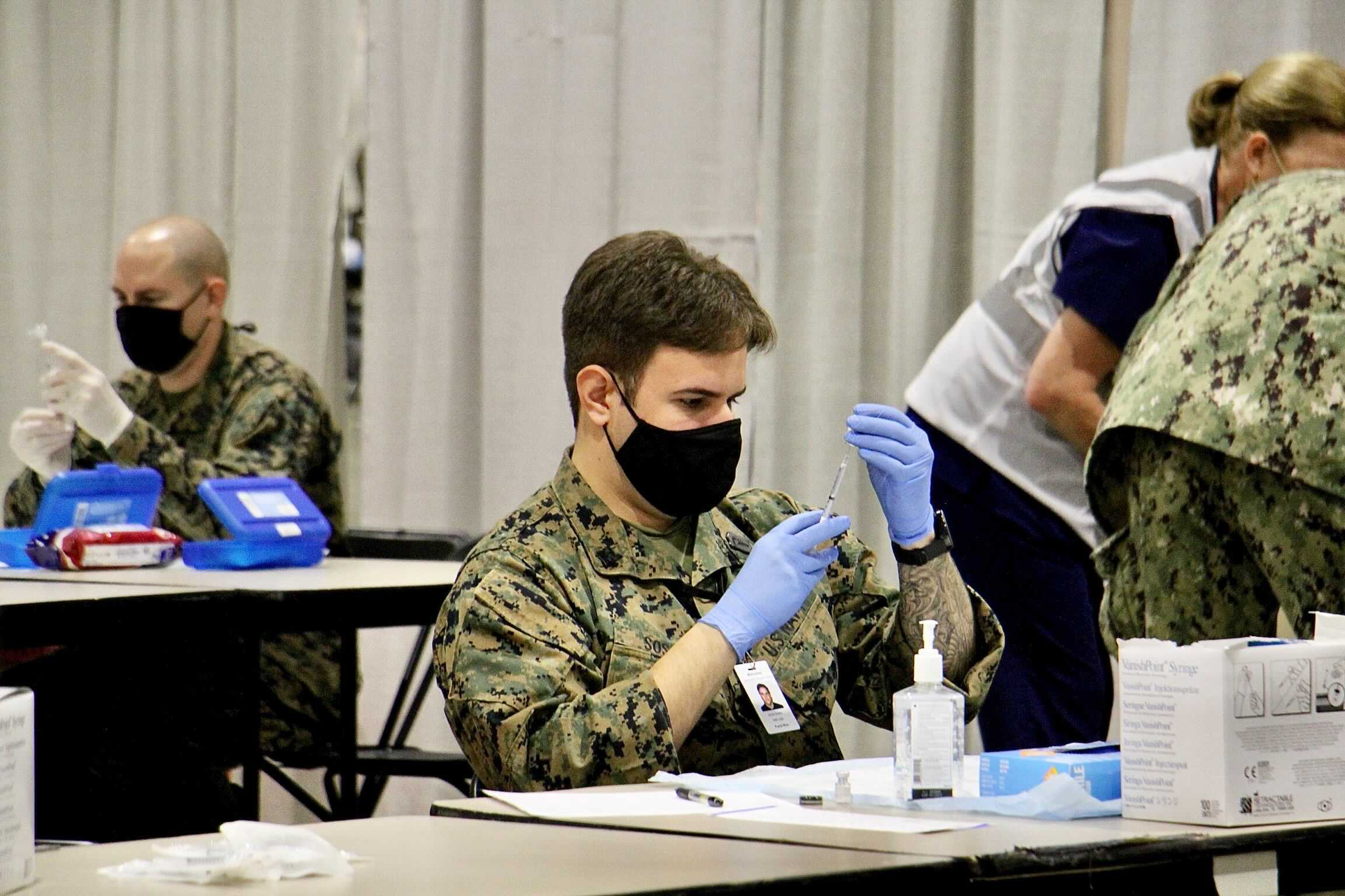 National Guard members fill syringes at the federally-run COVID-19 vaccination site