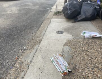Pizza menus litter a South Philadelphia block. (WHYY)